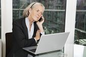 Senior businesswoman with laptop using cell phone while sitting at table