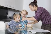 Mother with children baking and tasting cookie batter in kitchen