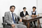 Portrait of Asian male with female colleagues in background at desk in office