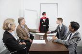 Business leader as superhero in front of colleagues at meeting in conference room