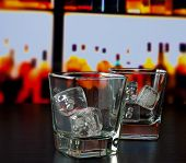 Empty Whiskey Glasses With Ice On Bar Table