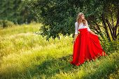 woman in red skirt standing under the tree