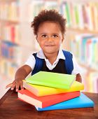 Little clever preschooler in the library, reading books, cute African American boy preparing to go t