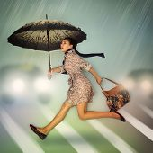 Autumn in the city. Young woman running cross the road at the pedestrian crossing holding umbrella a