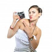 Beautiful girl takes her self picture with retro photo camera, over white.