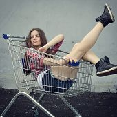 Happy beautiful teen girl driving shopping cart outdoor, image toned and noise added.