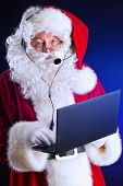 Portrait of a modern Santa Claus in headset standing with a laptop. Over dark background.