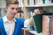 College student on university campus picking book from shelf