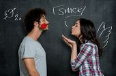 picture of hand kiss  - Woman Giving Flying Kiss To Her Boyfriend With Lip Sign On Cheek Over Gray Background - JPG