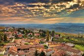 Small italian town among hills under beautiful cloudy autumnal sky at sunset in Piedmont, Northern I