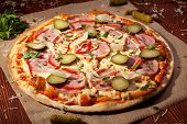 Pizza with Ham, Pickled Cucumber, Tomatoes and Mozzarella Cheese