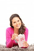 Girl eating popcorn and lying on a carpet isolated on white background