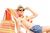 Shirtless young man sitting on a sun lounger isolated on white background