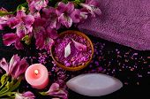 Spa and wellness setting with natural bath salt in bowl, orchid and towel