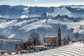 Small rural church and vineyards covered with snow in Piedmont, Northern Italy.