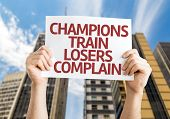 Champions Train Losers Complain card with a skyscraper background