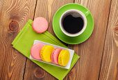 Colorful macaron cookies and cup of coffee on wooden table background