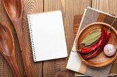 Wood kitchen utensils over wooden table background with notepad for copy space