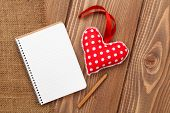 Blank notepad for copy space and vintage handmaded valentines day toy heart over wooden background