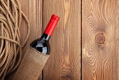 Red wine bottle over rustic wooden table background. View from above with copy space