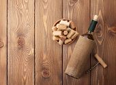 White wine bottle, bowl with corks and corkscrew. View from above over rustic wooden table background