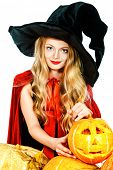 Pretty teen girl with blonde hair in a costume of witch posing with pumpkins. Halloween. Isolated over white background.