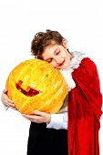 Cool teen boy in a costume of vampire posing with pumpkin with different emotions. Halloween.