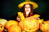 foto of teen smoking  - Pretty teen girl in a costume of witch standing with pumpkins over dark smoky background - JPG
