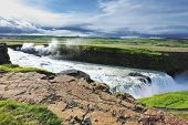 Iceland. Grand Gullfoss. In mid-July, bubbling water illuminated by a bright morning sun