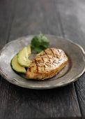 grilled chicken with cilantro and avocado on metal plate with copyspace