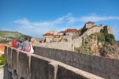 DUBROVNIK, CROATIA - MAY 26, 2014: People walking on the city walls with old houses in background. City wall is one of most popular tourist attraction in Dubrovnik.