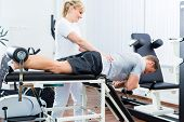Patient at the physiotherapy doing physical exercises with therapist with sport doctor