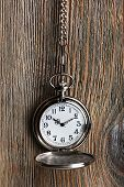 Silver pocket clock on wooden background