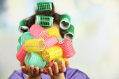 Girl in hair curlers on bright background