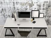 3D Rendering of Modern stylish black and white desk in an office interior with a desktop computer, office supplies and blank picture frames against a wall with abstract grey pattern, high angle view