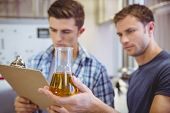 Two men looking at the beaker with beer in the factory