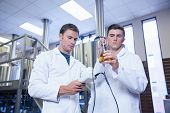 Two men in lab coat testing beer in the beaker in the factory