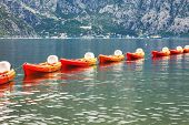 Row of kayaks in the sea on a background of mountains