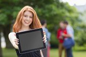 Pretty student smiling at camera using tablet pc at the university