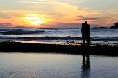 couple hugging and watching the sunset.