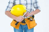Cropped image of technician holding hammer and hard hat over white background