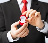 man making proposal with wedding ring in red gift box