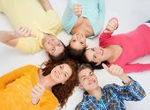 friendship, youth, gesture and people - group of smiling teenagers lying on floor in a circle and showing thumbs up
