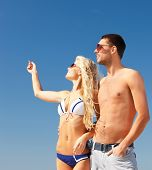 picture of happy couple in sunglasses on the beach, focus on man
