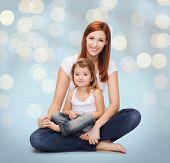 childhood, motherhood, parenting and relationship concept - happy mother with adorable little girl over holidays lights background