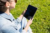 lifestyle, summer, vacation, technology and people concept - close up of young girl with tablet pc sitting on grass in park
