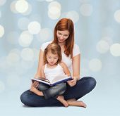 childhood, parenting and literature concept - happy mother with adorable little girl reading book over holidays lights background