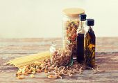 cooking and food concept - close up of two olive oil bottles and pasta in jars