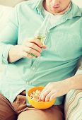 food, drinks, relax, leisure and people concept - close up of man with popcorn and beer sitting on couch at home