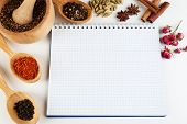 Spices with recipe book on white background